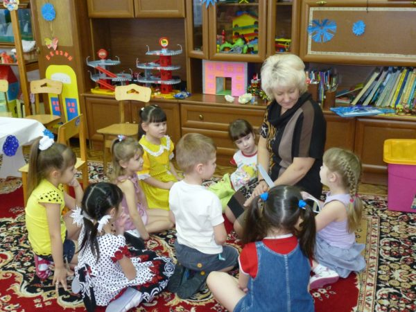 Дети и педагог сидят в кругу на ковре
