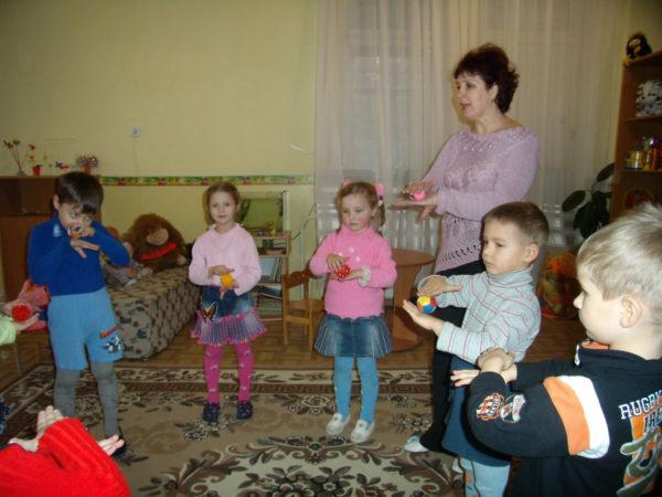 Дети и воспитатель играют с массажными мячиками