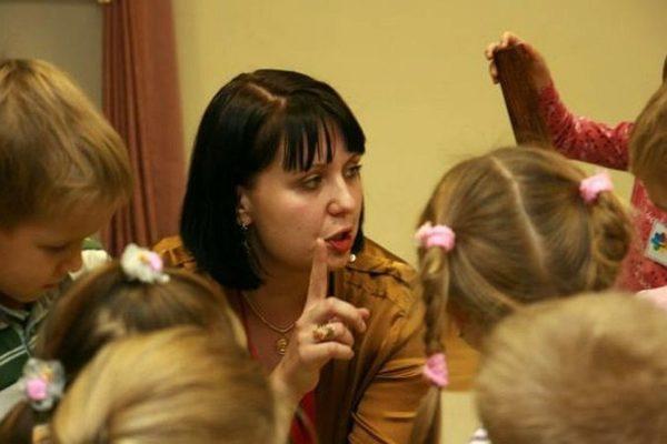 Воспитатель объясняет что-то детям, подняв вверх указательный палец