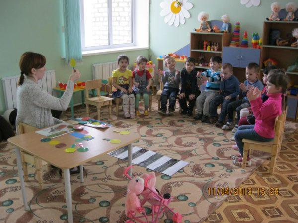 Воспитатель держит в руке жёлтый кружок светофора, дети выполняют задание