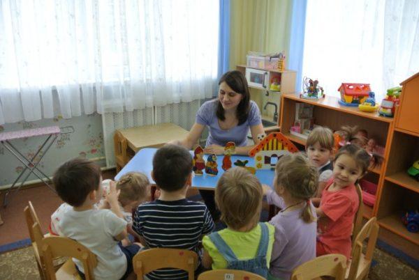 Воспитатель с помощью плоских фигурок рассказывает сказку детям, сидящим полукругом