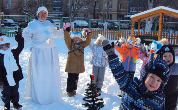 Дети и воспитатель в костюме снежной бабы на прогулке поднимают руки вверх
