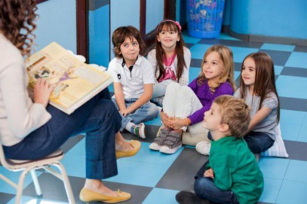 Воспитательница читает книгу сидящим на полу детям