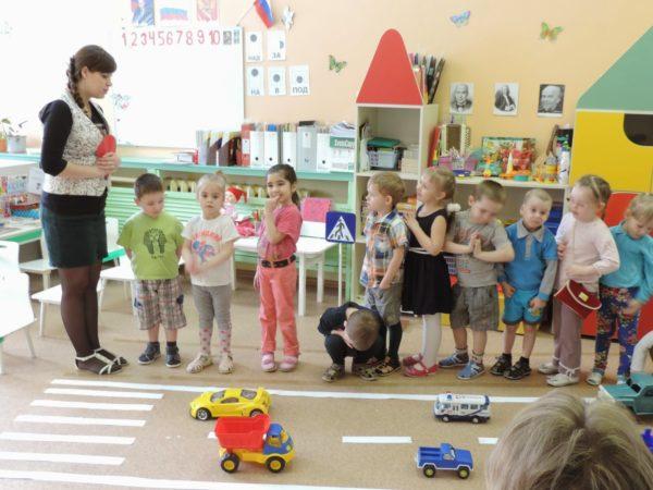 Воспитательница что-то говорит детям, стоящим перед макетом дороги в помещении группы