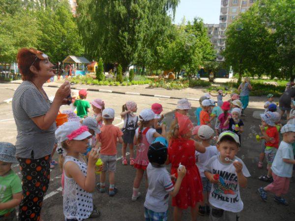 Воспитательница и дети дуют мыльные пузыри на улице