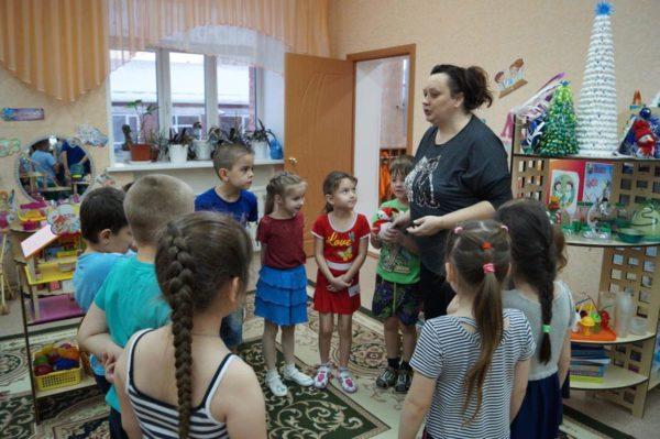 Воспитательница объясняет стоящим в кругу детям правила игры