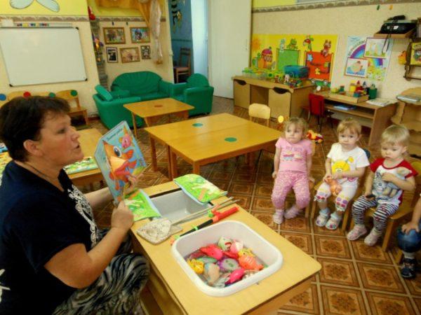 Воспитательница показывает картинку и объясняет