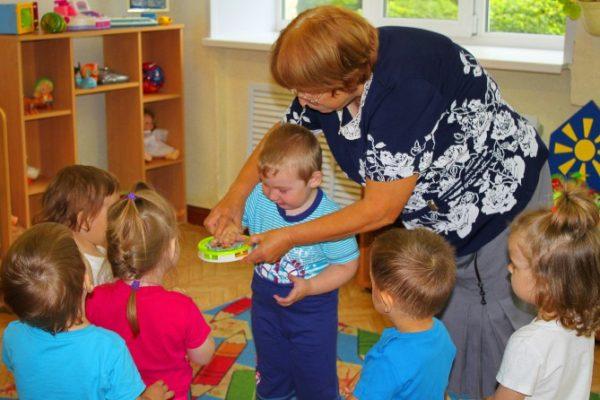 Воспитательница показывает мальчику, как играть на бубне, дети наблюдают