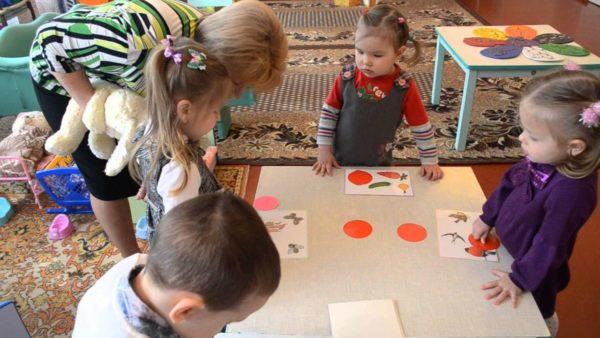 Воспитательница помогает девочке накрыть оранжевым кругом лишний объект