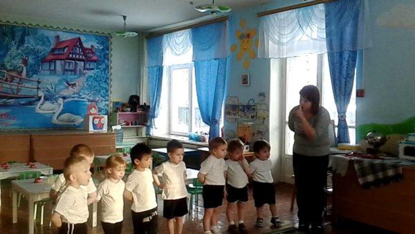 Воспитательница рассказывает что-то ребятам в белых футболках и чёрных шортах