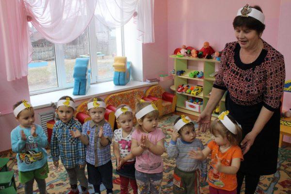 Воспитательница с детьми в бумажных шапочках с изображениями цыплят