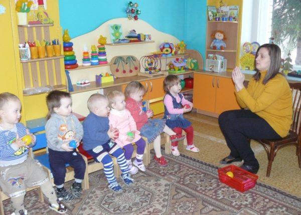 Воспитательница, сложив ладони вместе вверх, показывает детям пальчиковое упражнение