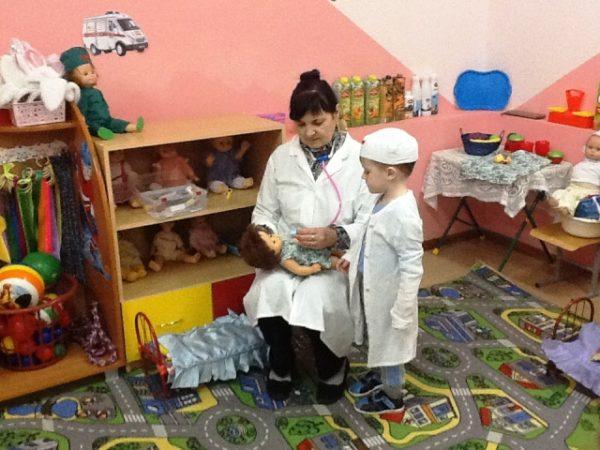 Воспитательница в белом халате объясняет мальчику, как пользоваться фонендоскопом