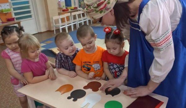 Воспитательница в русском сарафане помогает детям обрисовывать шаблоны мордочек животных