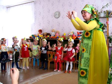 Воспитательница в жёлтом сарафане с подсолнухами и дети