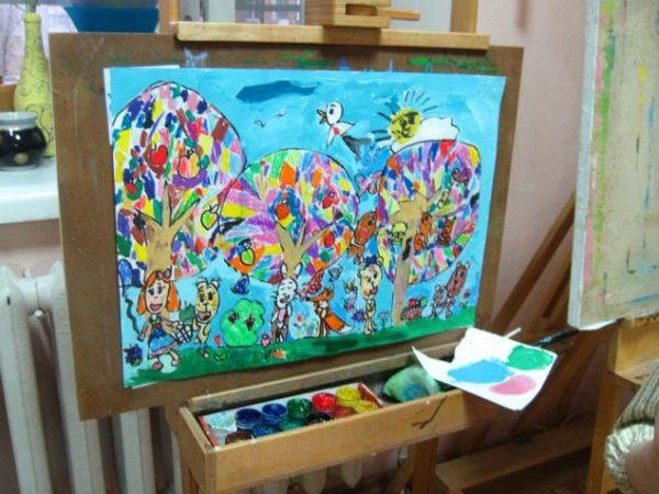 Яркая картина, нарисованная красками, на мольберте