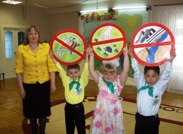 Дети держат запрещающие знаки для отдыхающих на природе, педагог стоит рядом