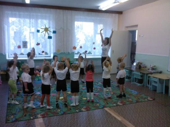 Дети и воспитательница подняли вверх руки