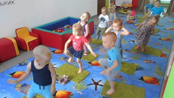 Дети идут по массажным коврикам