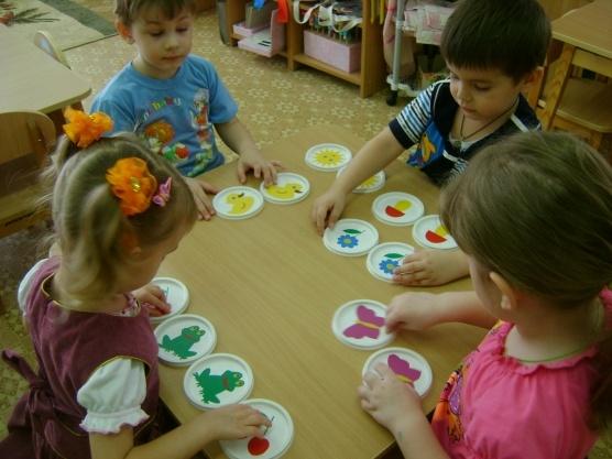Дети играют в настольную экологическую игру на крышках