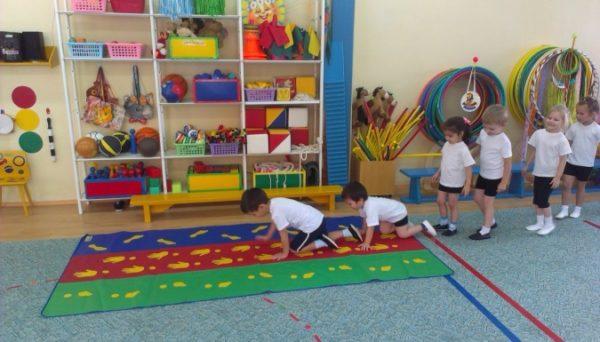 Дети по очереди ползут по коврику
