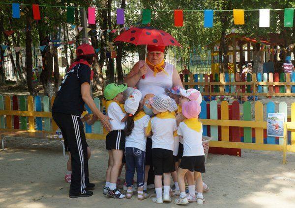 Дети под зонтиком-мухомором с воспитательницей