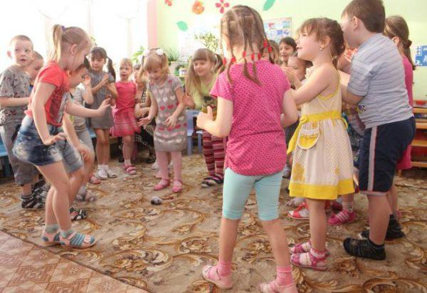 Дети, стоя в кругу, хлопают в ладоши