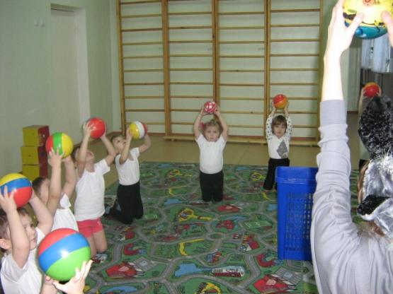 Дети выполняют упражнение с мячом в спотивном зале