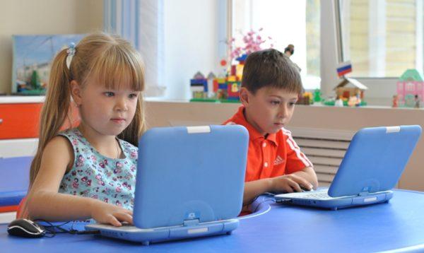 Девочка и мальчик сидят с голубыми лэптопами