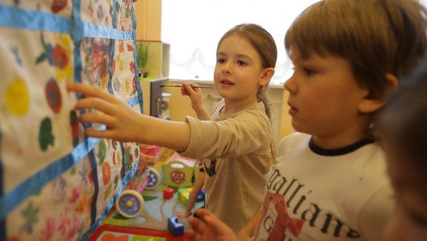 Девочка показывает мальчику элемент узора на картинке на стене