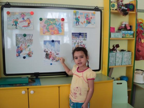 Девочка показывает на картинки на магнитной доске