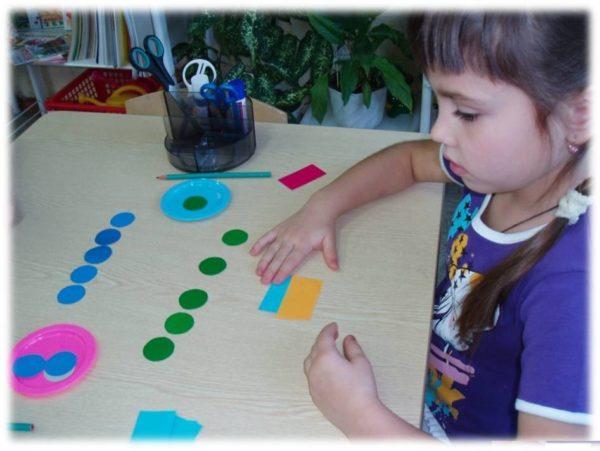 Девочка работает с раздаточным материалом по математике
