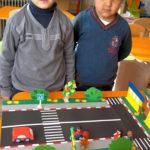 Два мальчика стоят у макета проезжей части