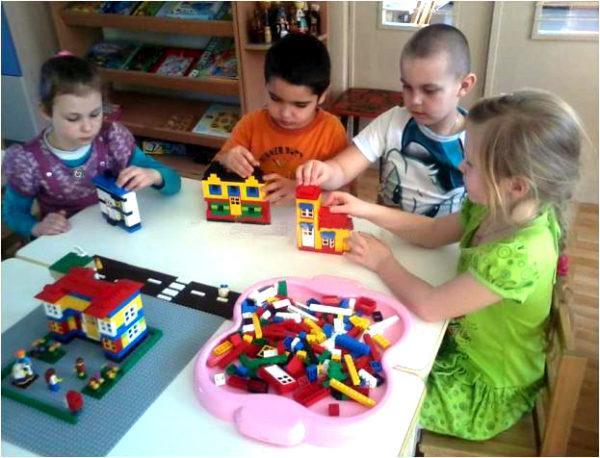 Четверо детей конструируют здания
