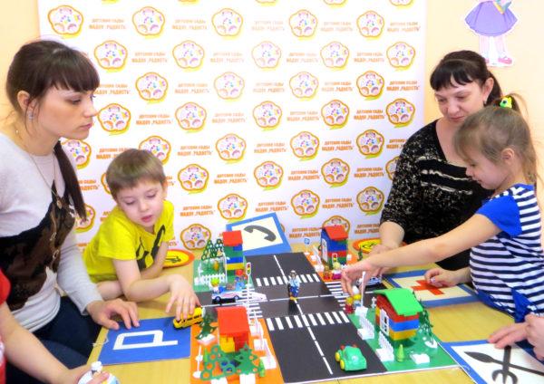 Дошкольники и их родители играют с макетом проезжей части
