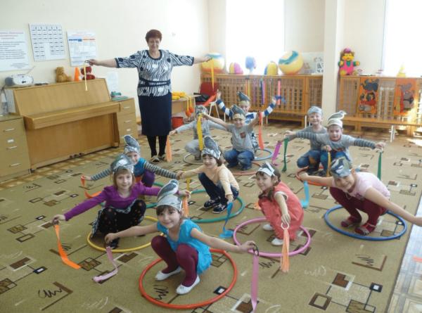 Дети в образах птичек играют в подвижную игру с обручами