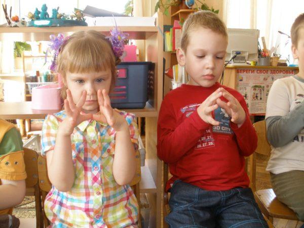 Мальчик и девочка выполняют пальчиковое упражнение «Пирамидка»