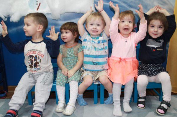 Пятеро смеющихся малышей сидят на стульчиках