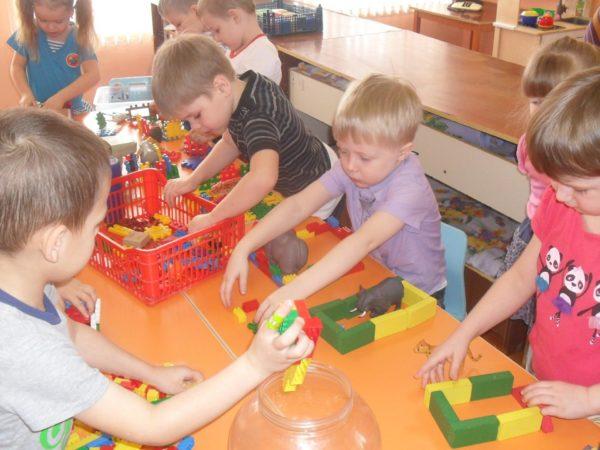 Дети строят из конструктора загоны для животных