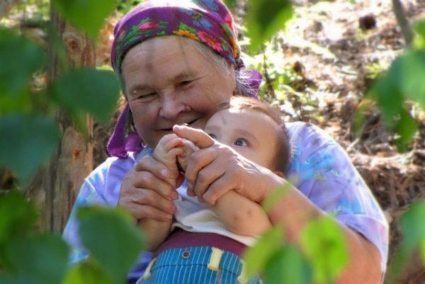 Бабушка играет с малышом в пальчиковую игру