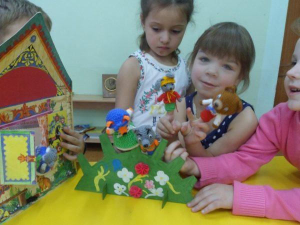 Трое детей разыгрывают сказку «Теремок» с помощью пальчикового театра