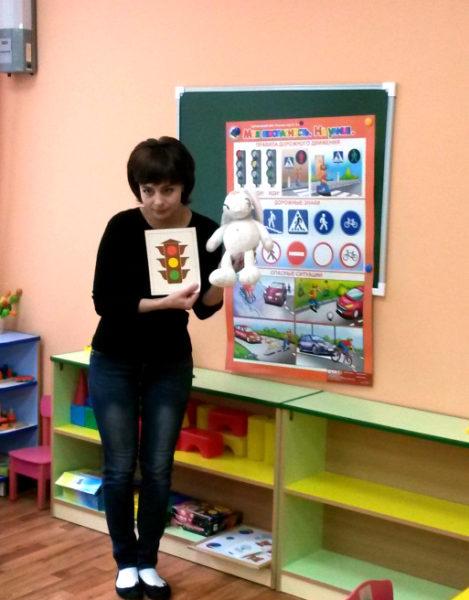 Педагог держит в руках игрушку и картинку с изображением светофора
