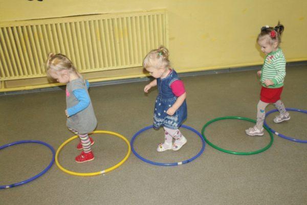 Три девочки идут по разложенным на полу хулахупам