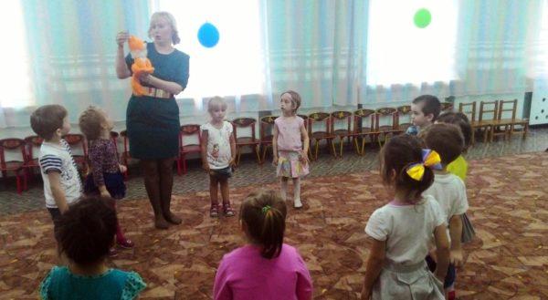 Воспитатель рассказывает что-то детям, стоящим в кругу, от лица игрушки