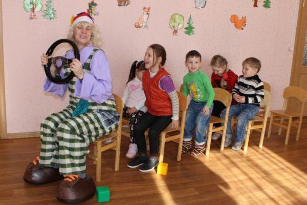Педагог в костюме клоуна играет с детьми в автобус