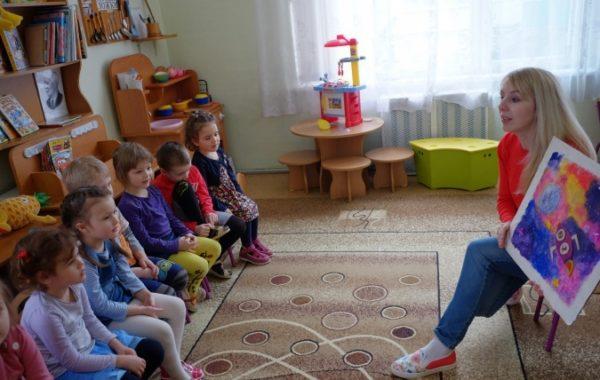 Воспитательница показывает детям рисунок с ракетой в космосе