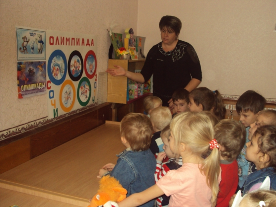 Воспитательница показывает на картинку с олимпийскими кольцами