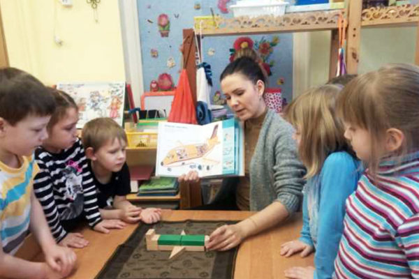 Дети и педагог конструируют модель самолёта из деревянного строительного материала