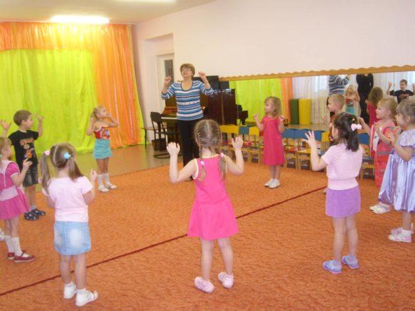 Педагог и дети выполняют упражнение с поднятыми вверх ладошками