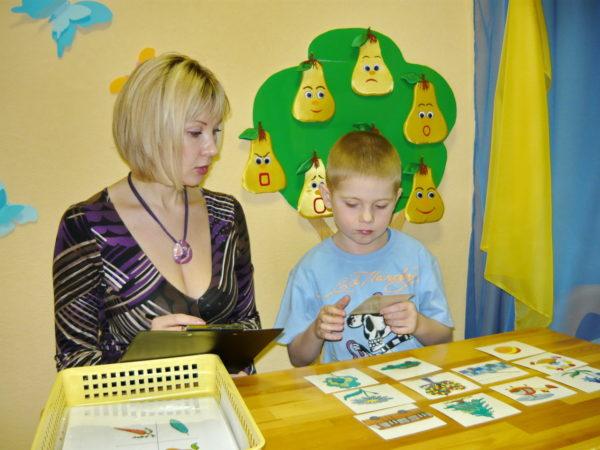 Мальчик выполняет задание с карточками, педагог наблюдает